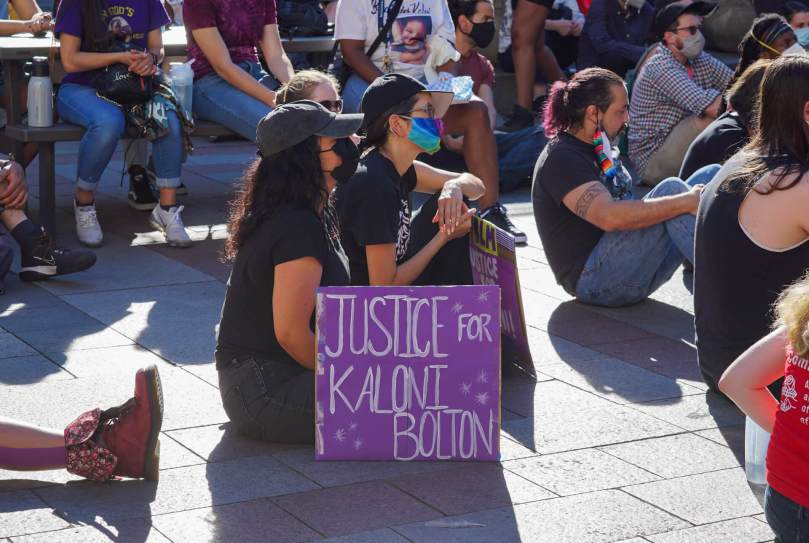"""Individuals sit and listen to speakers beside a purple sign that reads in white text """"Justice for Kaloni Bolton"""" at the #BreatheforKaloni rally."""