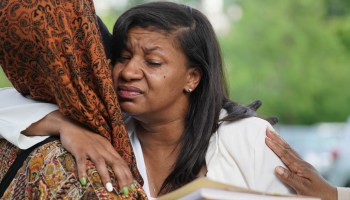 Lorenzo Anderson's mother Donnitta Sinclair revives a hug from a cousin during the celebration of Lorenzo's life.