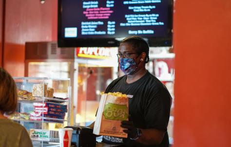 Justin Pritchett, managing director for Ark Lodge Cinemas, sells a customer some popcorn.
