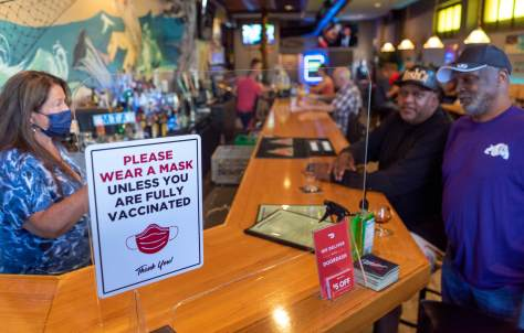 """Photo of a """"Please wear a mask unless you are fully vaccinated"""" sign at the front of the Beachcomber's bar."""