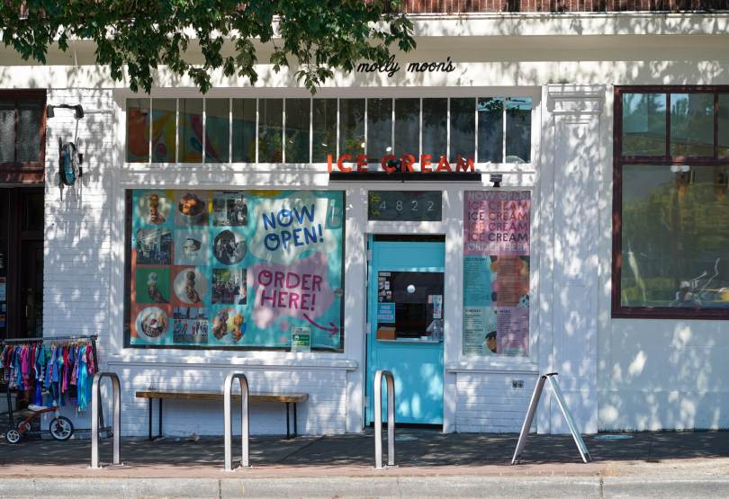 """Photo of the exterior of Molly Moon's Ice Cream in Columbia City with its window showing colorful pastel signs that read """"NOW OPEN!"""" and """"ORDER HERE!"""""""
