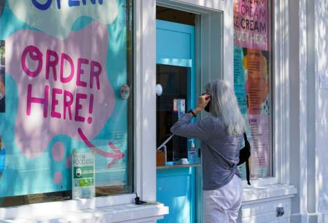 A customer puts her mask on before ordering ice cream at Molly Moon's
