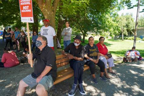 Community members listen to speeches during the rally