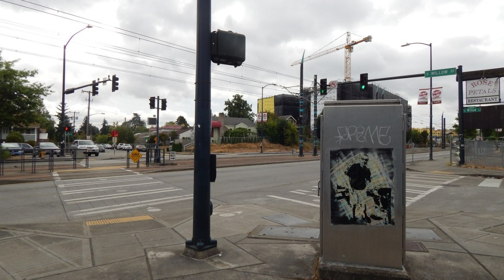 Photo of an intersection in the Othello Neighborhood with a street art on power box.