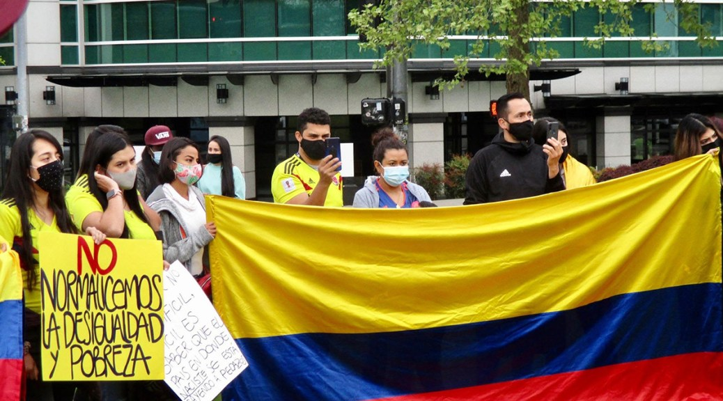 Photo depicting a solidarity protest between protestors in Seattle and Colombia. Protestors carry the Colombian flag.