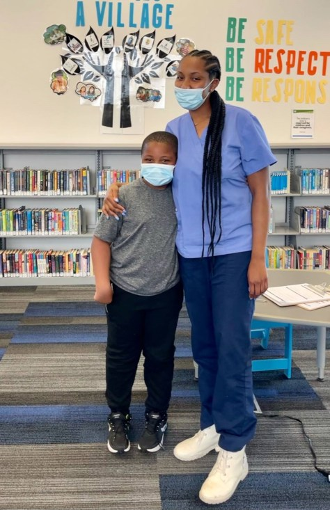 A Black female-presenting individual and a Black youth wearing blue surgical facemasks pose in front of a library bookshelf.