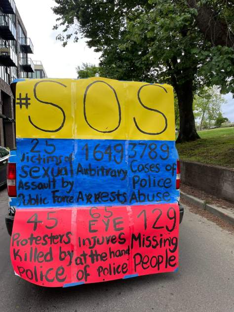 """Photo depicting a protest sign in the colors of the Colombian flag (yellow, blue, and red) with text that reads """"#SOS"""" as well as statistics for all of the police brutality leveled against protestors in Colombia."""