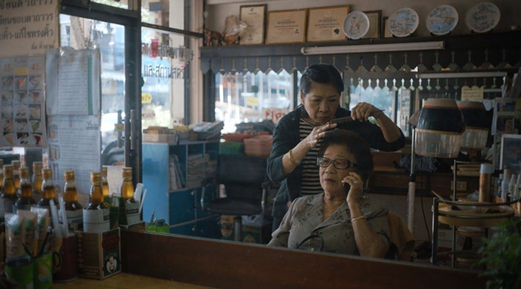 Photo depicting Ninlawan Pinyo sitting in a hairdresser's chair on her cell phone while the hairdresser works on her hair.