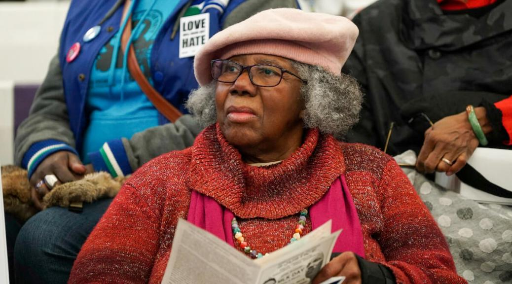 Reverend Harriet Walden, a Black elder, wears a pink hat and a red sweater. Photo by Susan Fried