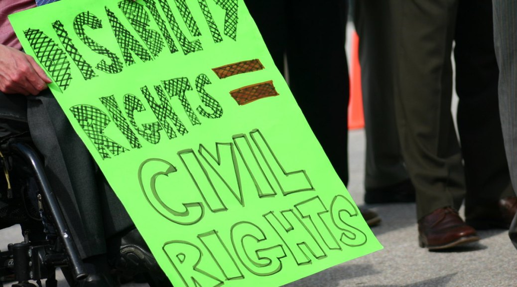 """Neon green protest sign with handwritten letters that read """"Disability Rights = Civil Rights"""""""