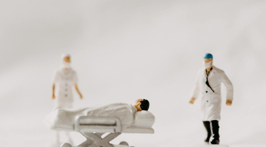 Photo depicting medical figurines, one doctor, one nurse, and a patient on a hospital bed, posed against a white background.