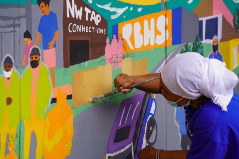 Photo depicting an individual carefully applying yellow paint to a mural alongside a building.