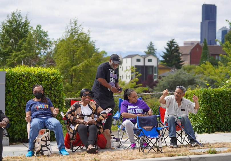 Photo of Black-presenting individuals sitting in lawn chairs along 23rd Avenue waiting for a parade to begin.