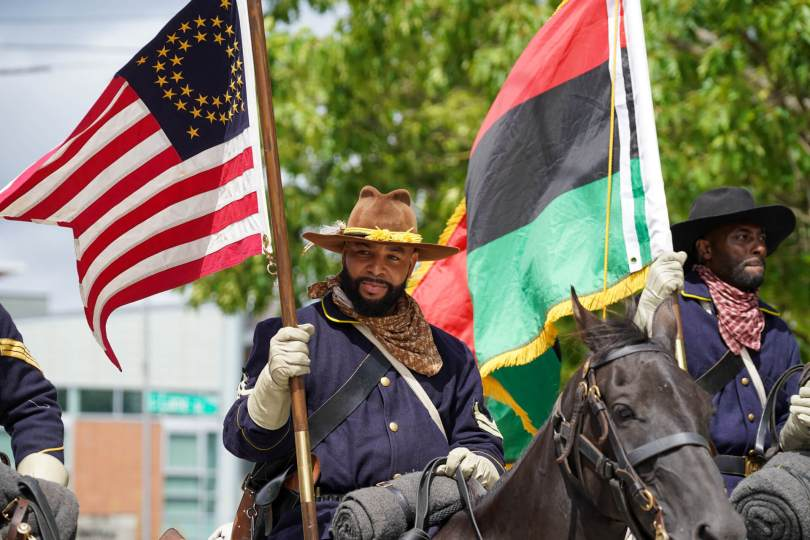Photo of the Buffalo Soldiers of Seattle on horseback carrying flags for the Umoja Day of Unity and Black Love Parade.