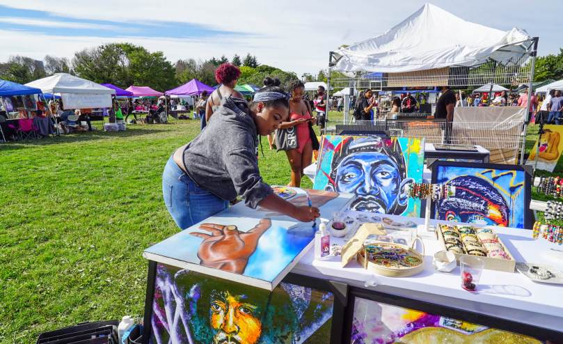 Photo of Devon, aka Art Deity, working on a brightly colored painting at her booth in Jimi Hendrix Park.