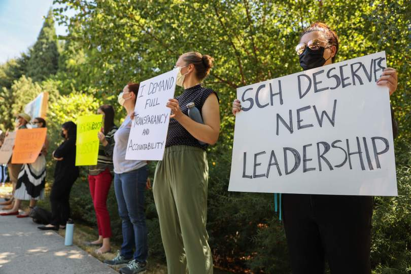 """Photo of female-presenting individuals standing in a line carrying protest posters; the one nearest the foreground reads, """"SCH DESERVES NEW LEADERSHIP."""""""