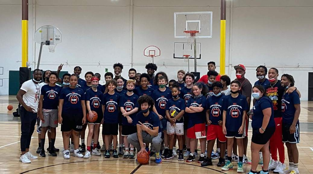 """Photo depicting a group of youth posing behind a squatting C.J. Elleby in a basketball gymnasium. All the youth are wearing """"C.J. Elleby Youth Basketball Camp"""" t-shirts."""