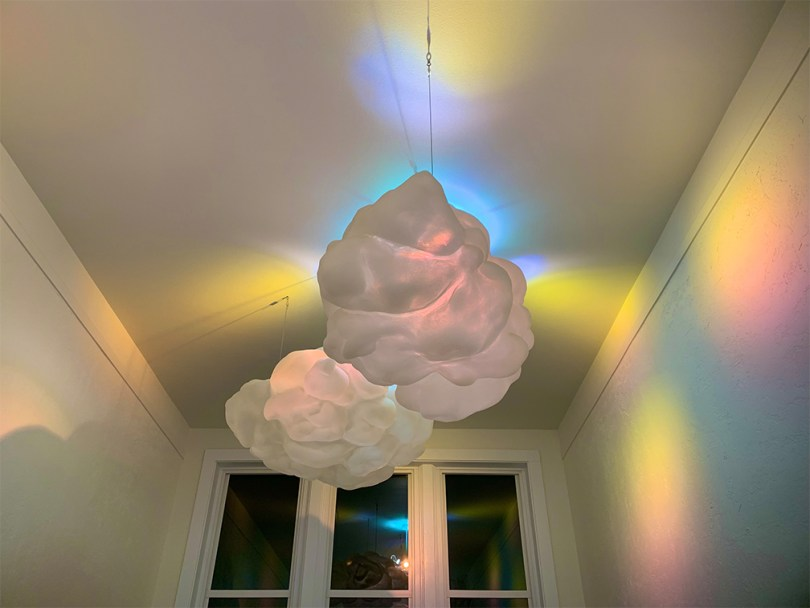 """Photo depicting Louis Chinn's artwork called """"Gathering Radiance"""" at night. The artwork is two sculpted clouds hanging from the ceiling that give off brightly colored spotlights."""
