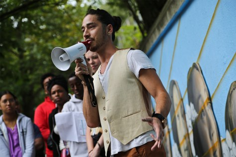 Photo depicting Louis Chinn speaking into a small megaphone in front of a street mural.