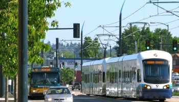 Photo depicting a South Seattle street with the 42-Downtown bus as well as Sound Transit light rail.