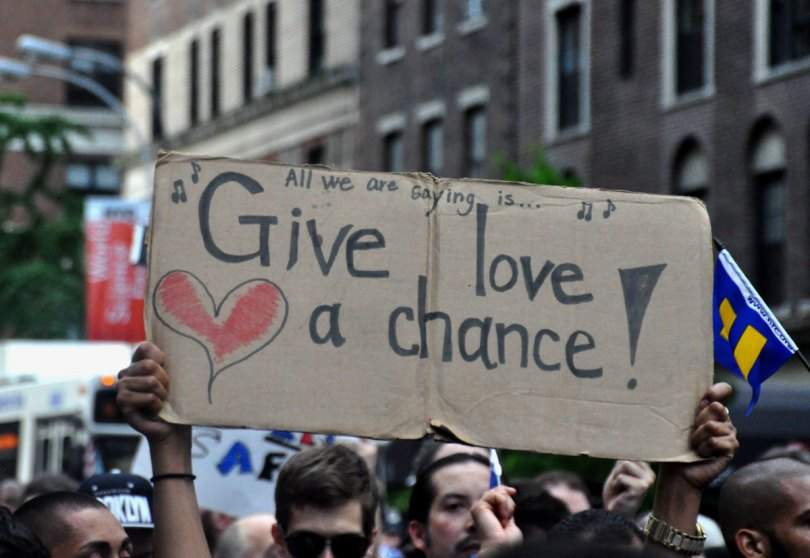 hands holding Give Love a Chance sign in crowd