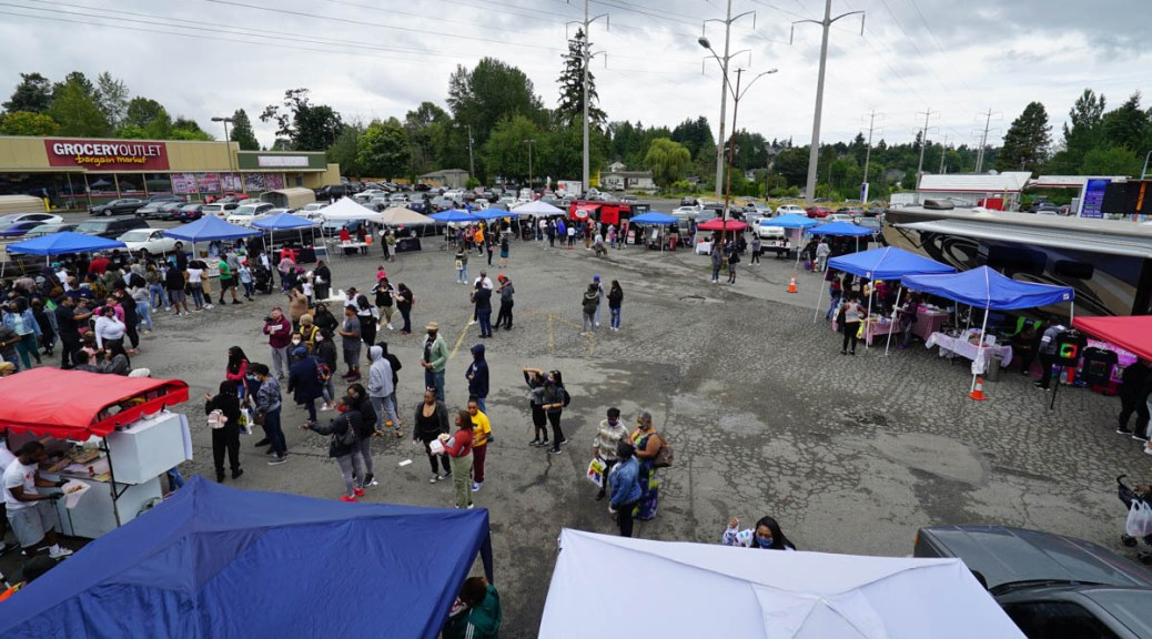 Photo of a parking lot filled with vendor tents and stalls with people lining up for them.