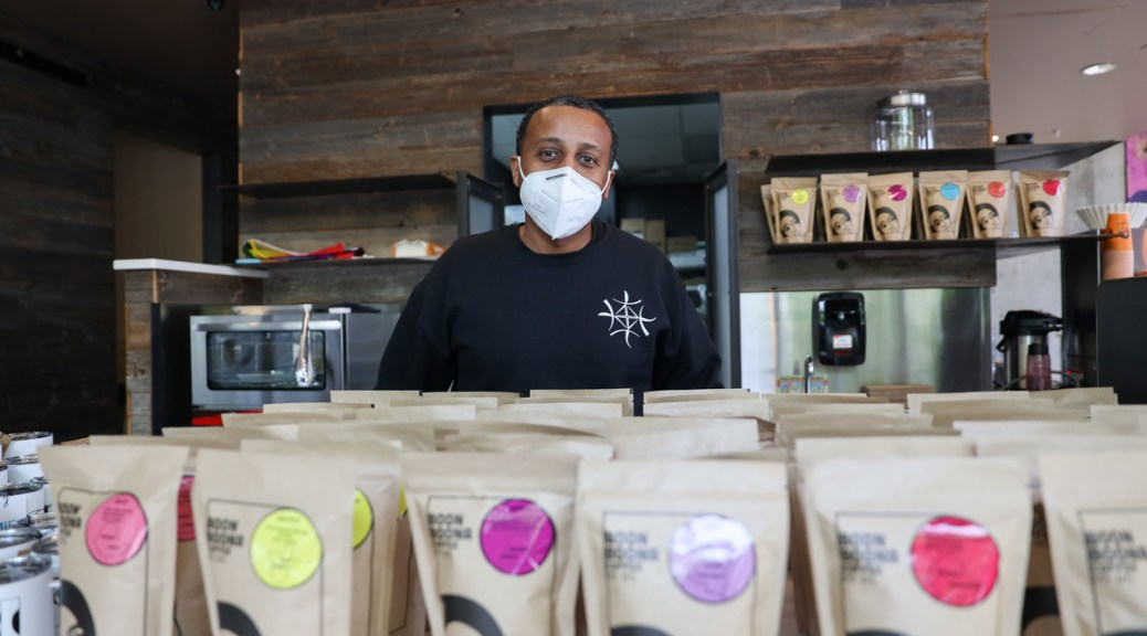 Photo of Efrem Fesaha wearing a face mask inside one of his coffee shops. Bags of Boon Boona coffee beans sit in front of him.