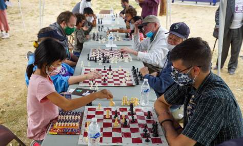 Photo depicting a long outdoor table with portable chess boards and individuals playing chess. In the foreground, a female-presenting youth in a pink t-shirt plays chess against an older male-presenting adult with glasses and a blue-and-green plaid collared shirt.