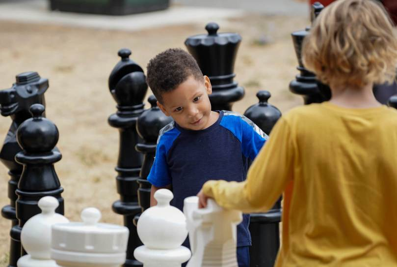Photo depicting a male-presenting youth in a blue t-shirt staring fascinated at a giant white Knight chess piece. Another youth in a yellow t-shirt rests their hand on the piece.