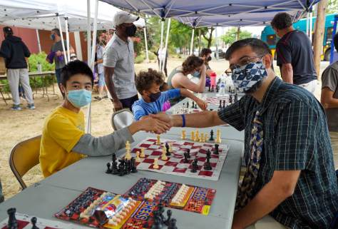 Photo depicting Edward Cheng in a yellow t-shirt and blue surgical face mask shaking hands with Josh Sinanan, who is wearing a chess-themed tie and face mask, over a chess board.
