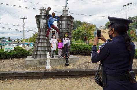 """Photo depicting Seattle Police Detective Denise """"Cookie"""" Bouldin taking a picture of some of her chess club members standing in front of a metal sculpture with two giant chess pieces in front of the group."""