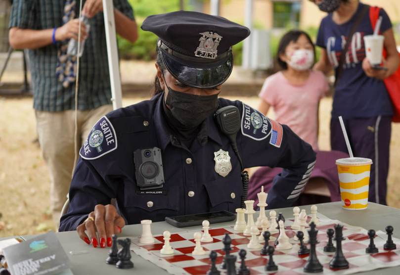 """Photo of Detective Denise """"Cookie"""" Bouldin in her SPD uniform thinking over a chess board."""