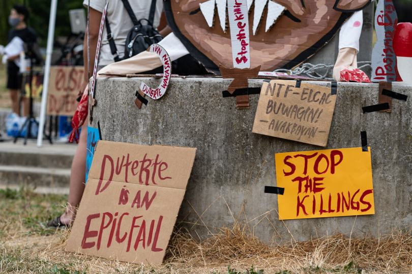 """Signs that read """"Duterte is an EPIC FAIL,"""" """"Stop the Killings,"""" and """"NTF-ELCAC BUWAGIN! ANAKBAYAN"""" on display at Othello Park."""