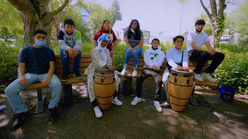 Photo depicting youth sitting on a park bench, two of them posing with tall traditional drums.