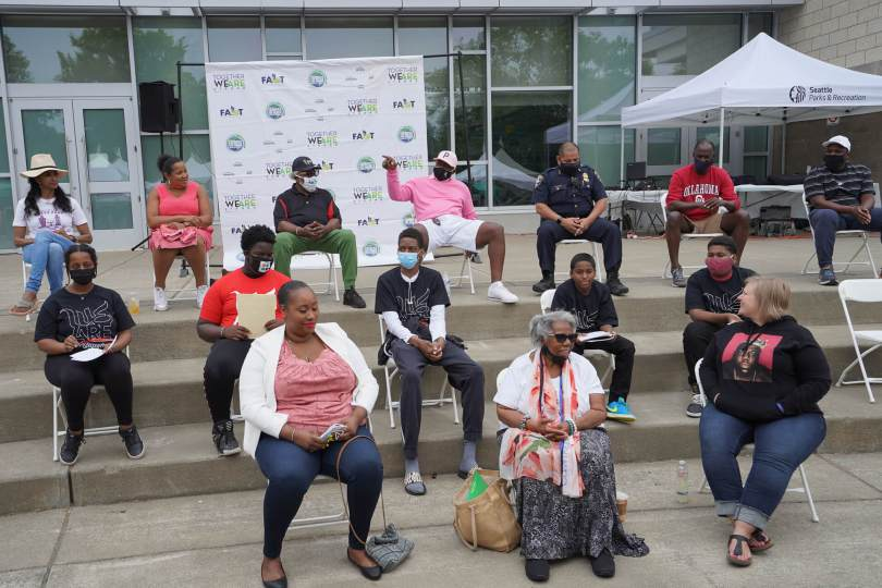 Members of the community, Seattle Police Department, and youth gather on the steps of the Rainier Beach Community Center to discuss a panel on gun violence