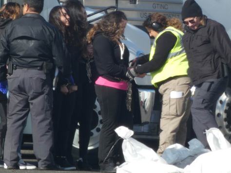Photo of ICE Air personnel handcuffing migrants on the tarmac.