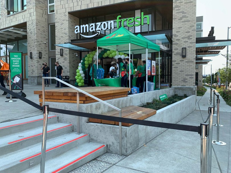 Entrance of the Amazon Fresh Jackson store on opening day. A green balloon arch stands at the doorway as well as two green pop-up tents with workers wearing dark green shirts.