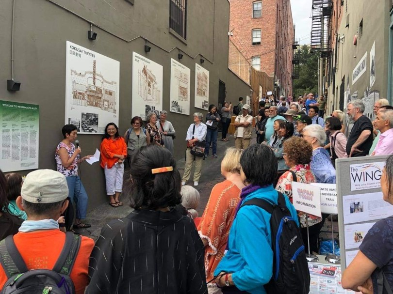 Photo depicting a crowd of people gathered in an alleyway listening to a female-presenting individual speaking into a microphone in front of a wall with architectural art.