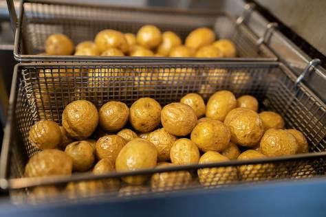 Photo of fresh potatoes in steel baskets.