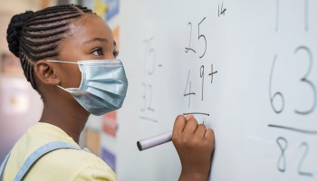 Photo depicting a Black schoolgirl wearing a blue surgical face mask solving addition problem on white board during the Covid-19 pandemic.