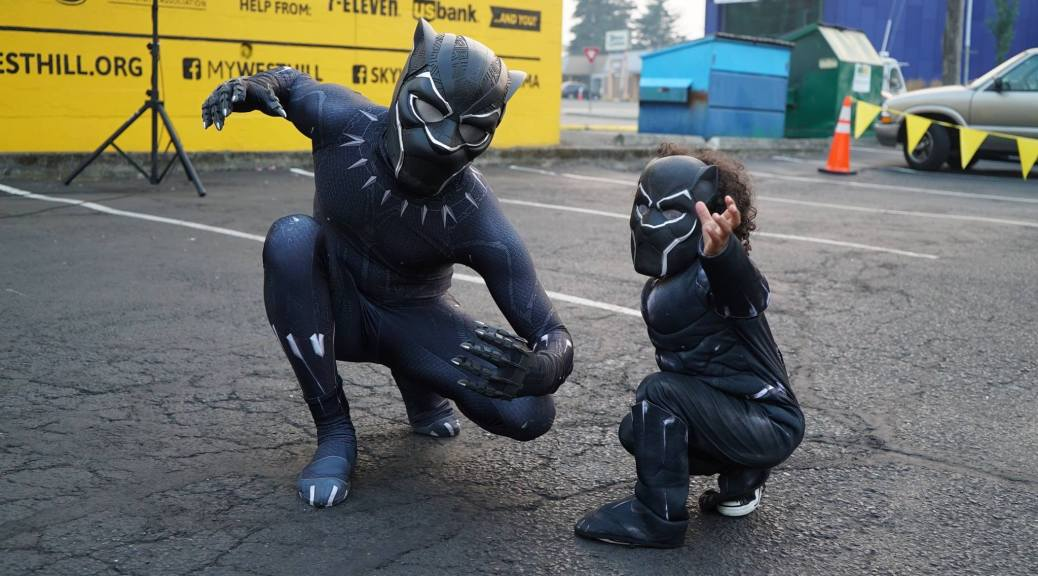 Photo of two individuals (on the right a small youth/toddler) dressed as Marvel's Black Panther.