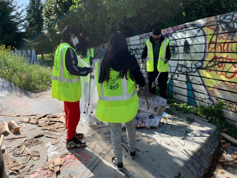 Photo depicting youth in reflective jackets by a graffitied wall collecting litter.