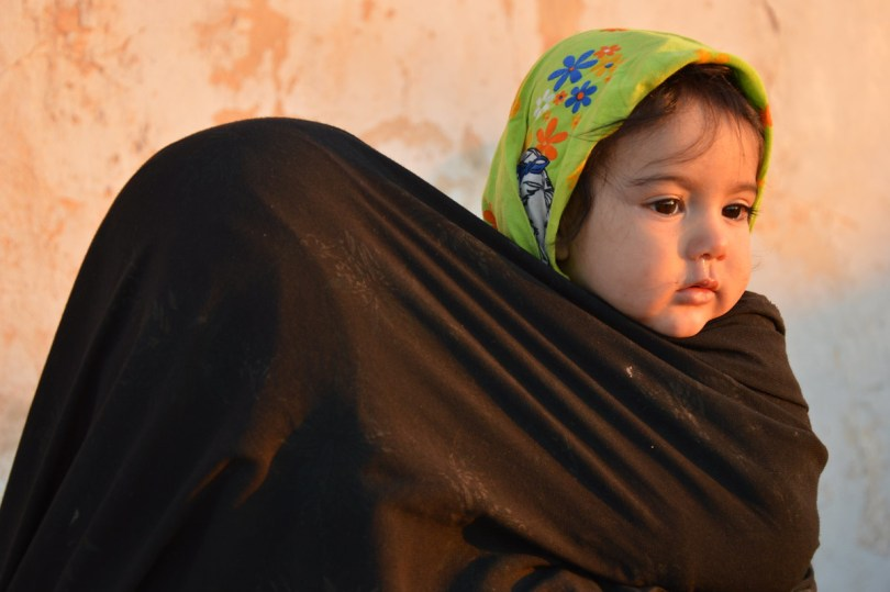 photo of a mother in a burqa carrying a small child