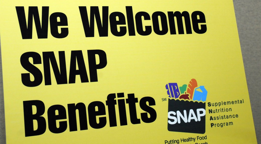 """Photo depicting a yellow sign with black text that reads """"We Welcome SNAP Benefits."""" Additional text at the bottom right corner depicts a vector-image of a filled grocery bag with the word """"SNAP"""" written on it with the tagline """"Supplemental Nutrition Assistance Program: Putting Healthy Food Within Reach."""""""