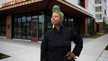 Kristi Brown, a Black woman, stands outside the Liberty Bank building in a black chef's coat and a colorful head wrap. Courtesy of the Frye.