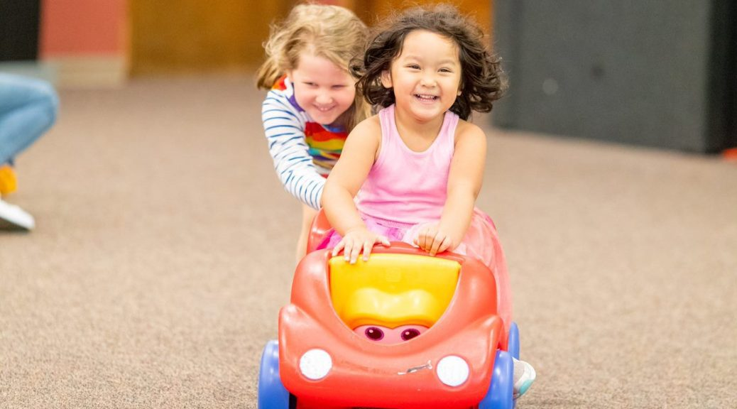 Photo depicting two female-presenting youth, one pushing the other on a red toy car.