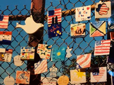 Photo depicting a wire fence covered in tribute tiles created by school children for the fallen of 9/11.