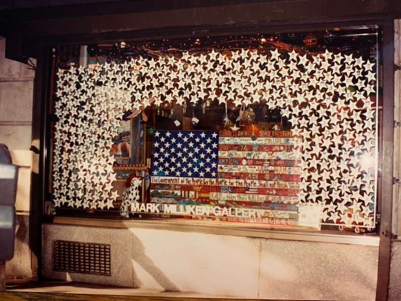 Photo depicting the Mark Milliken Gallery window filled with an American flag and white stars dedicated to the fallen first responders of 9/11.