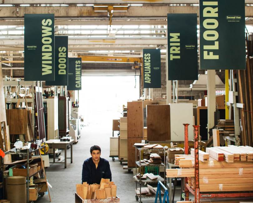 Photo depicting the interior of Second Use with green signs indicating aisles for windows, doors, cabinets, appliances, trim, and flooring. An individual pushes a bin full of wooden slabs down the center aisle.