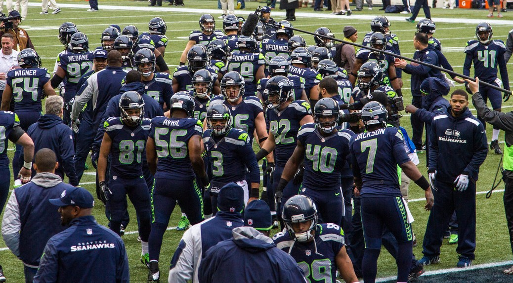 Photo depicting players of the Seattle Seahawks grouped together on a football field.